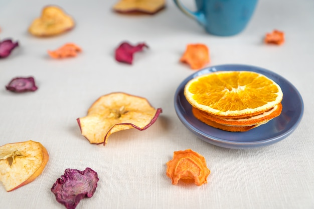 Zdrowe odżywianie organiczne. pokrojony i wysuszony jabłko, pomarańcze, marchewka i burak na tekstylnym tle.