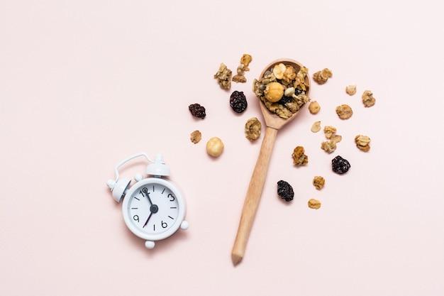 Zdrowe odżywianie. pieczona granola z owsa, orzechów i rodzynek w drewnianej łyżce i budzik na różowym tle. widok z góry