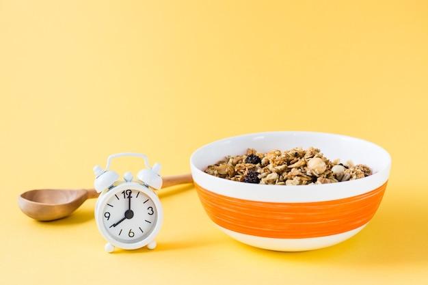 Zdrowe odżywianie. pieczone płatki owsiane, orzechy i rodzynki granola w misce, drewnianą łyżką i budzikiem na żółtym tle