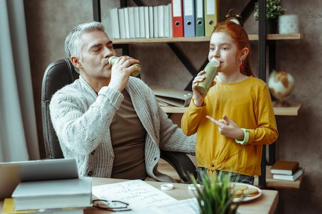 Zdrowe odżywianie. pozytywna wesoła dziewczyna uśmiecha się, delektując się pysznym koktajlem z ojcem