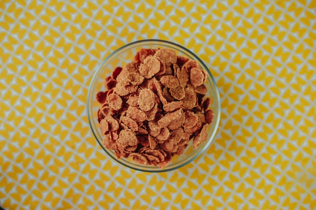 Zdrowe odżywianie, zdrowe jedzenie na stole, ciemne płatki zbożowe w szklanej misce na żółtym stole.
