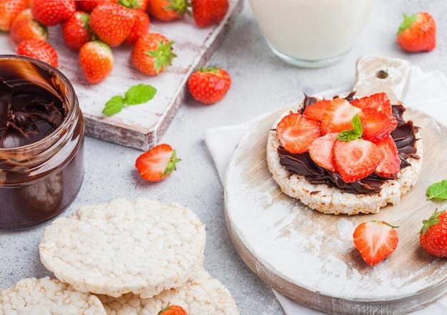 Zdrowe organiczne ciastka ryżowe z masłem czekoladowym i świeżymi truskawkami na desce i szklance mleka