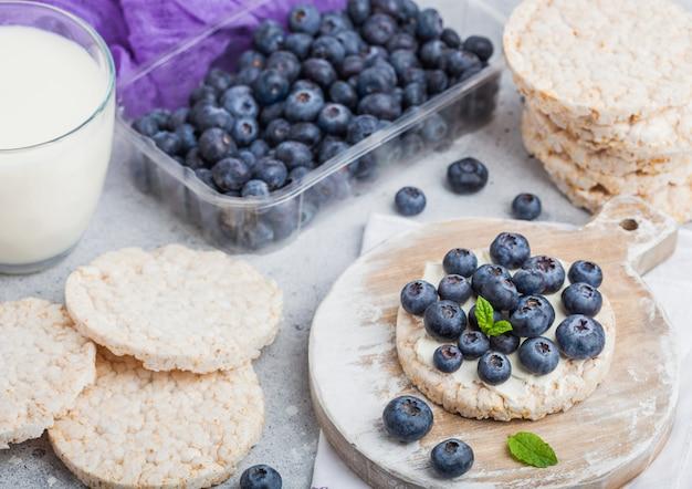 Zdrowe organiczne placki ryżowe z ricottą i świeżymi jagodami i szklanką mleka
