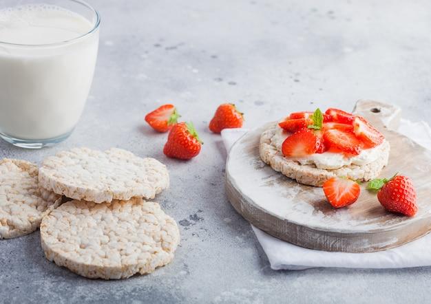 Zdrowe organiczne placki ryżowe z ricottą i świeżymi truskawkami i szklanką mleka