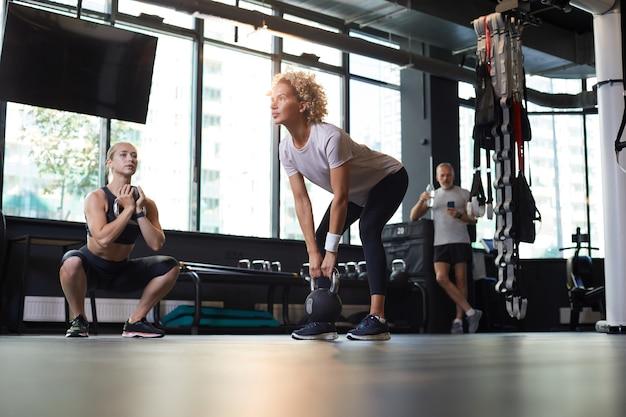 Zdrowe osoby ćwiczące z hantlami podczas treningu na siłowni