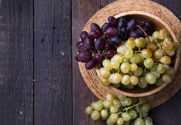 Zdrowe owoce czerwone i białe winogrona do wina na drewnianych powierzchniach