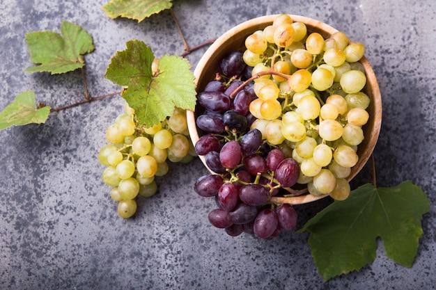 Zdrowe owoce czerwone i białe winogrona do wina na powierzchni kamienia s