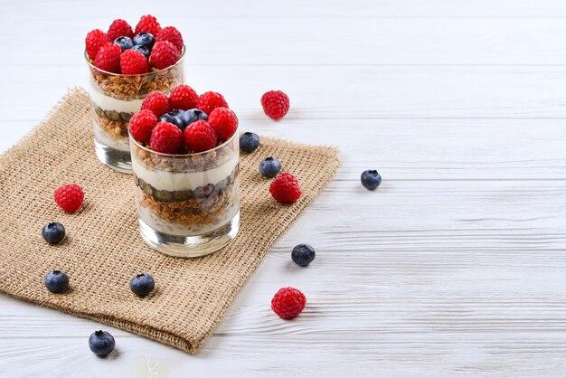 Zdrowe parfait jagodowo-malinowe w szklance na rustykalnym białym stole z drewna