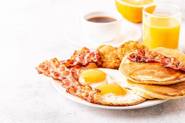 Zdrowe pełne śniadanie amerykańskie z jajkami naleśniki bekonowe i latkes, selektywne focus.