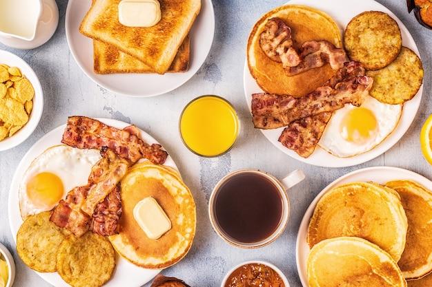 Zdrowe pełne śniadanie amerykańskie z jajkami, naleśniki z bekonem i latkes, widok z góry.