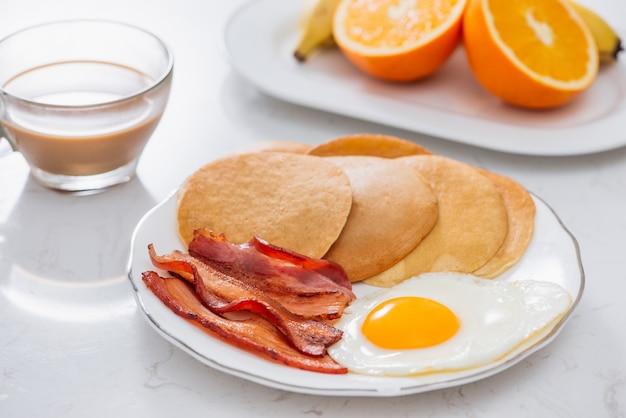 Zdrowe, pełne śniadanie amerykańskie z jajkiem na bekonie i naleśnikami
