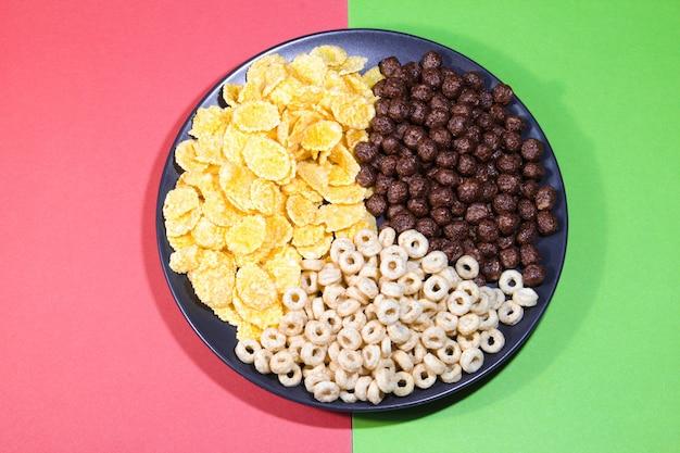Zdrowe pierścionki płatki kukurydziane i czekoladowe kulki w czarnym talerzu na kolorowym tle