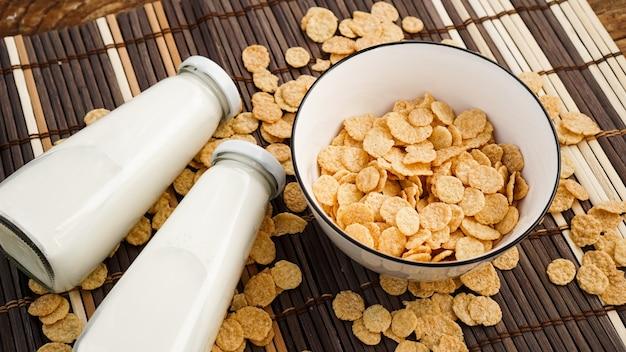 Zdrowe płatki kukurydziane i mleko na bambusowej serwetce. szklana butelka z mlekiem na zdrowe śniadanie