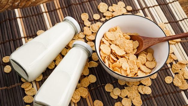 Zdrowe płatki kukurydziane i mleko oraz drewniana łyżka na bambusowej serwetce. szklane butelki z mlekiem na zdrowe śniadanie