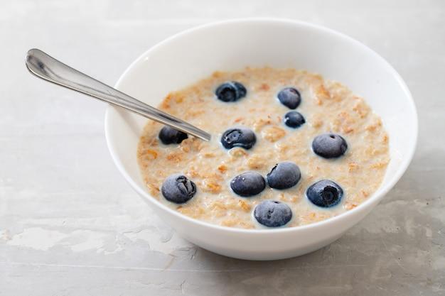 Zdrowe płatki pszenne z mlekiem i jagodami w białej misce