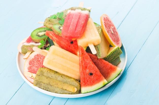 Zdrowe popsicles z całych owoców z jagodami kiwi arbuz kantalupa na drewnianym stole vintage