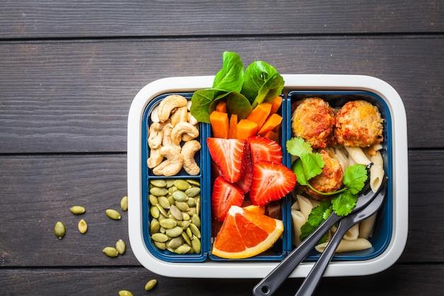 Zdrowe posiłki pojemniki prep z klopsikami fasoli, makaronu, warzyw, jagód, nasion i orzechów w pojemniku