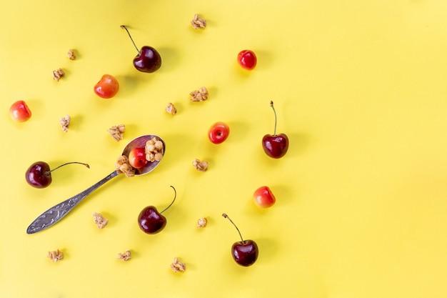 Zdrowe posiłki śniadaniowe na żółtym stole, kopia przestrzeń. płatki kukurydziane, musli, jagody i łyżka, widok z góry.