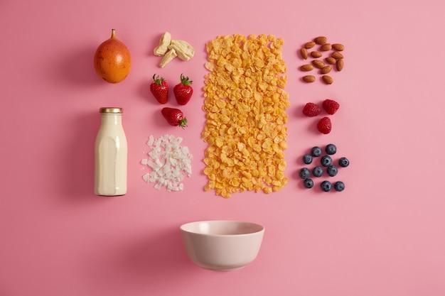 Zdrowe produkty śniadaniowe. pożywne płatki zbożowe, świeże mleko, jagody, owoce egzotyczne i suszone owoce do przygotowania dietetycznej owsianki. ekologiczne pyszne składniki zawierające wiele niezbędnych składników odżywczych.