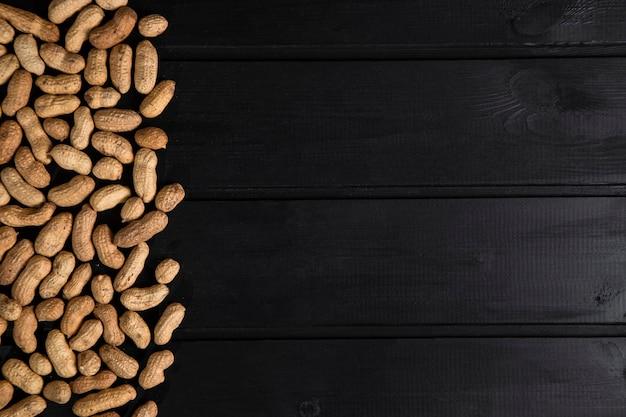 Zdrowe przekąski orzechy orzeszki ziemne umieszczone na ciemnym drewnianym stole. wysokiej jakości zdjęcie