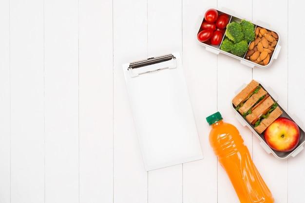 Zdrowe pudełka na lunch z kanapką, świeżymi warzywami, owocami i orzechami na białym tle drewnianych. widok z góry