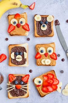 Zdrowe śmieszne kanapki dla dzieci. tosty ze zwierzęcych twarzy z masłem orzechowym i czekoladowym, orzechami laskowymi, jagodami orientacja pionowa. ścieśniać. widok z góry.