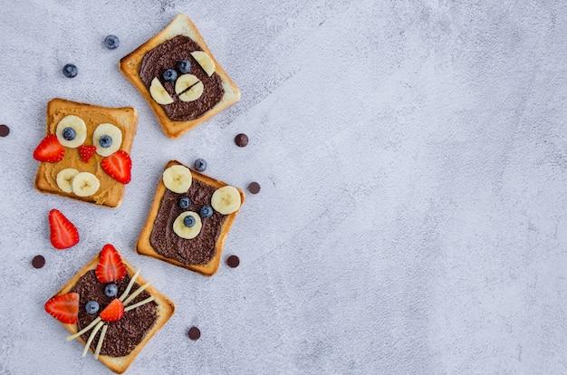 Zdrowe śmieszne kanapki dla dzieci. tosty ze zwierzęcych twarzy z masłem orzechowym i orzechowym, bananem, truskawką i jagodą.