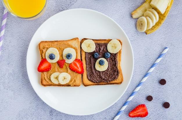 Zdrowe śmieszne kanapki dla dzieci. tosty zwierzęce z masłem orzechowym i czekoladowym z orzechami laskowymi, bananem, truskawką i jagodą na białym talerzu z sokiem pomarańczowym. zamknij, widok z góry.