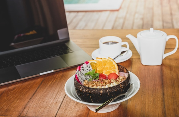 Zdrowe smoothie miskę śniadanie z laptopa na drewnianym stole.