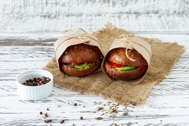 Zdrowe śniadanie - burger z wędzonym łososiem, liśćmi sałaty i awokado podawany w papierze rzemieślniczym na drewnianym tle, poziomy.
