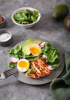 Zdrowe śniadanie dietetyczne keto paleo: jajko na twardo, awokado, ser halloumi, liście sałaty