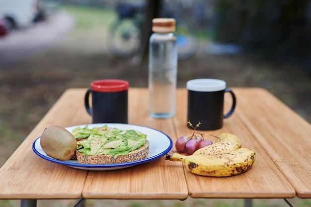 Zdrowe śniadanie dla dwojga na stole kempingowym z owocami, kawą i grzanką z awokado