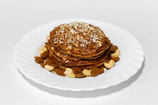 Zdrowe śniadanie, domowe amerykańskie wegańskie naleśniki z surowymi orzechami nerkowca i migdałami na białym talerzu.