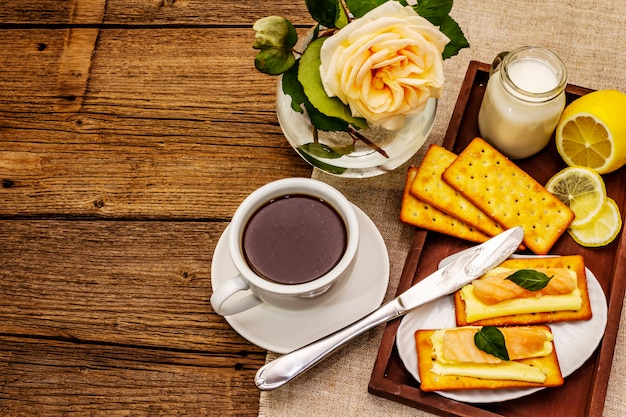 Zdrowe śniadanie. filiżanka kawy (czarna herbata), mleko, krakersy z masłem i łososiem