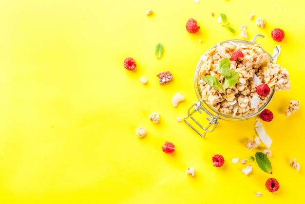Zdrowe śniadanie i przekąska koncepcja domowej roboty muesli ze świeżymi malinami w słoiku na jasnym żółtym tle