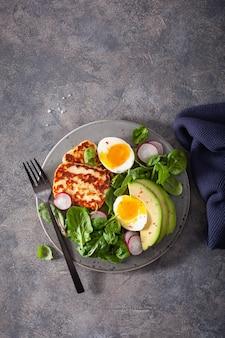 Zdrowe śniadanie: jajko na twardo, awokado, ser halloumi, liście sałaty