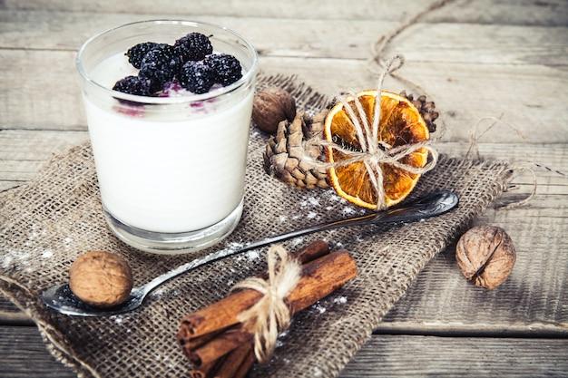 Zdrowe śniadanie - jogurt mleczny z malinami, morwy na drewnianym stole