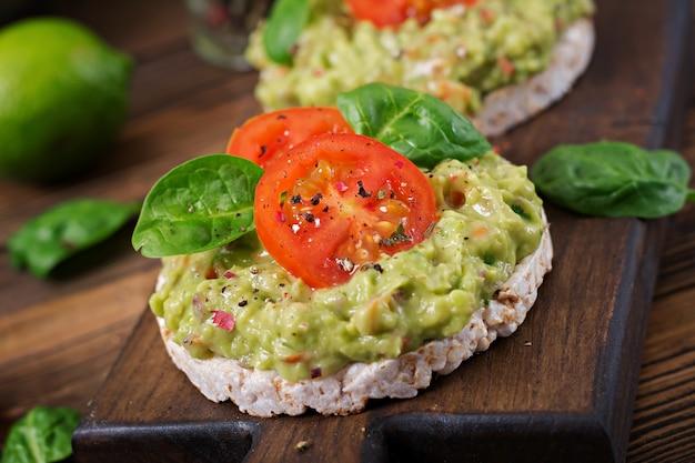 Zdrowe śniadanie. kanapka chrupiący chleb z guacamole i pomidorami na drewnianym stole.