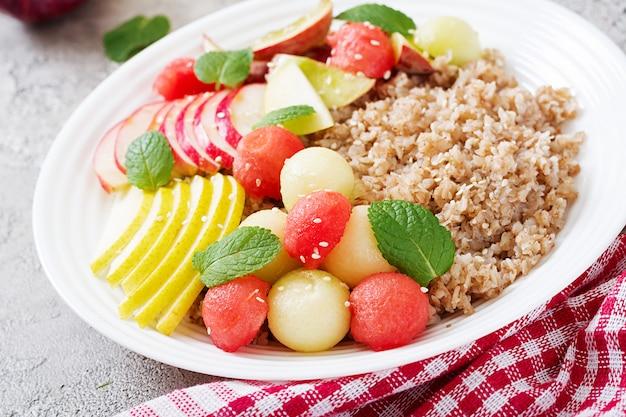 Zdrowe śniadanie. kasza gryczana lub owsianka ze świeżym melonem, arbuzem, jabłkiem i gruszką. smaczne jedzenie.
