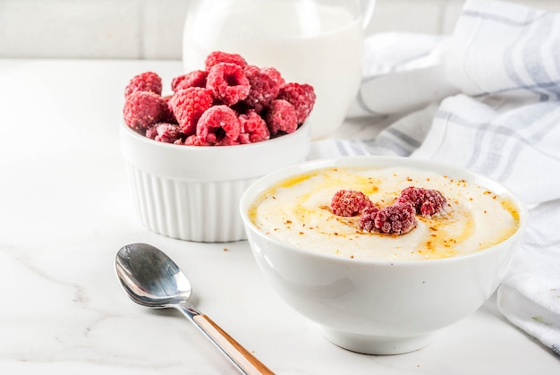 Zdrowe śniadanie, kasza manna z mlekiem i malinami, stół z białego marmuru