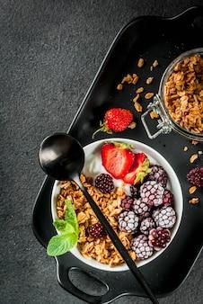 Zdrowe śniadanie. letnie jagody i owoce. domowy grecki jogurt z muesli, jeżynami, truskawkami i miętą. czarny kamienny stół z dodatkami. widok z góry