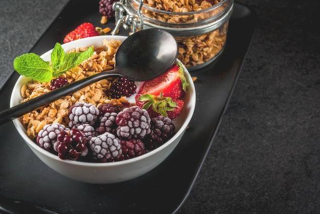 Zdrowe śniadanie. letnie jagody i owoce. domowy grecki jogurt z muesli, jeżynami, truskawkami i miętą. czarny kamienny stół z dodatkami.