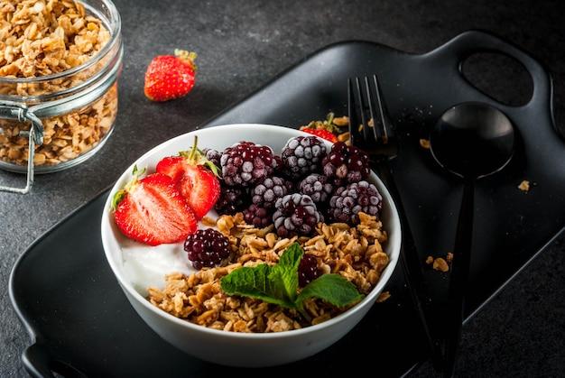 Zdrowe śniadanie. letnie jagody i owoce. domowy grecki jogurt z muesli, jeżynami, truskawkami i miętą. na czarnym kamiennym stole z dodatkami.