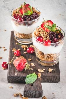 Zdrowe śniadanie. letnie jagody i owoce. domowy grecki jogurt z muesli, jeżynami, truskawkami, wiśniami i miętą. na białym betonowym kamiennym stole, w szklankach.