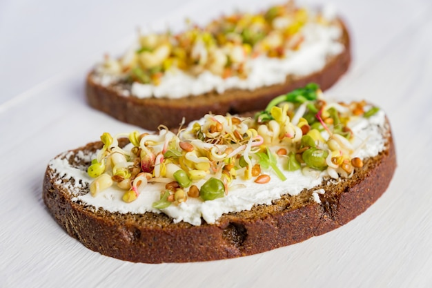 Zdrowe śniadanie makrobiotyczne. kanapka z twarogiem, mikrozielonymi groszkiem i kiełkami fasoli mung