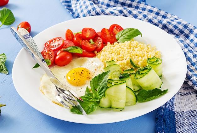 Zdrowe śniadanie. menu dietetyczne. kasza jaglana i pomidor, sałatka z ogórka i jajka sadzone.