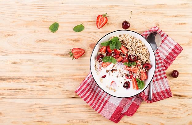 Zdrowe śniadanie - muesli, truskawek, wiśni, orzechów i jogurtu w misce na drewnianym stole. wegetariańskie jedzenie koncepcja. widok z góry