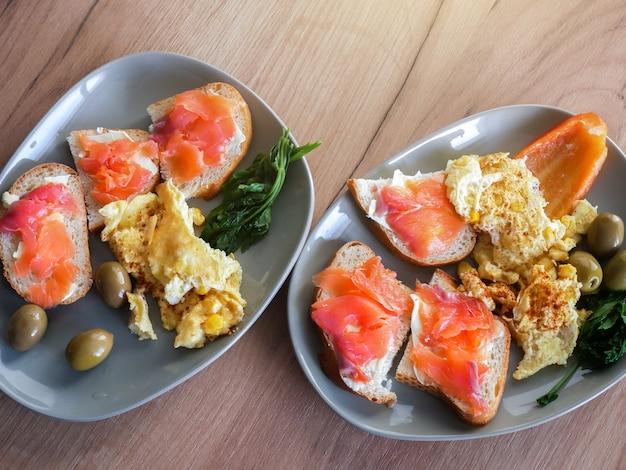 Zdrowe śniadanie. omlet z oliwkami, papryką i sałatką z rukoli. łosoś z chlebem razowym.