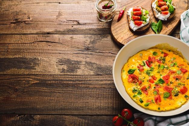 Zdrowe śniadanie omlet z pomidorkami koktajlowymi i szpinakiem na patelni i tostem z twarogiem, sosem pesto i pomidorkami cherry na brązowym drewnianym tle