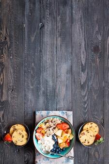 Zdrowe śniadanie, płatki z jogurtem, truskawki, jagoda, jabłko, banan, na rustykalne drewniane. widok z góry